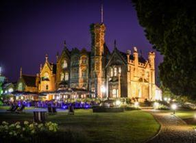 The exterior of Oakley Court, a hotel in Windsor, lit up at night