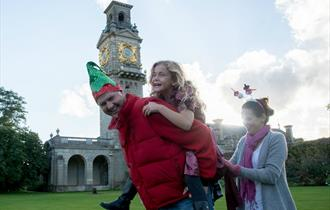 Family in Christmas costume in front of National Trust Cliveden's clocktower.